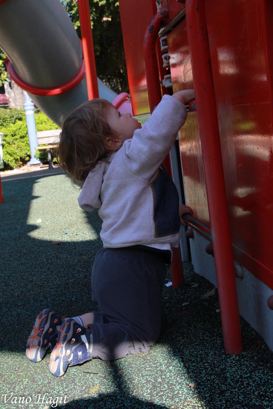 תינוק מטפס בגן שעשועים